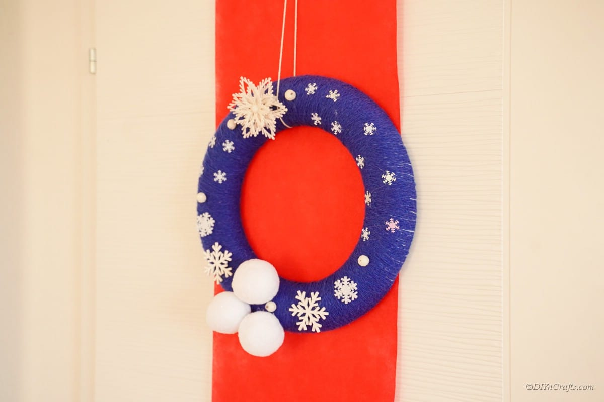 Wreath hanging over red background on wall