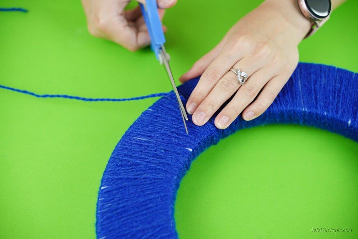 scissors cutting blue yarn