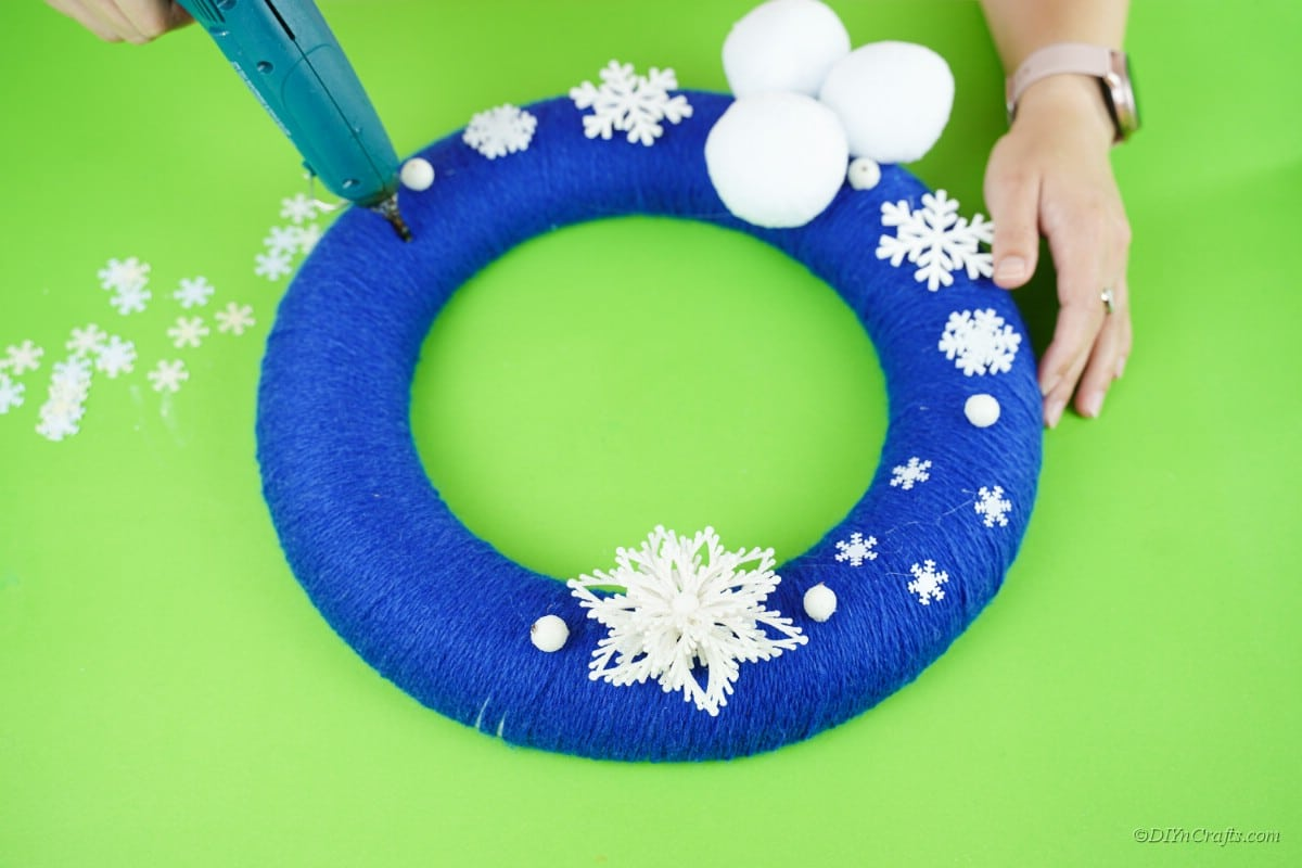 craft snowflakes being applied to a blue wreath