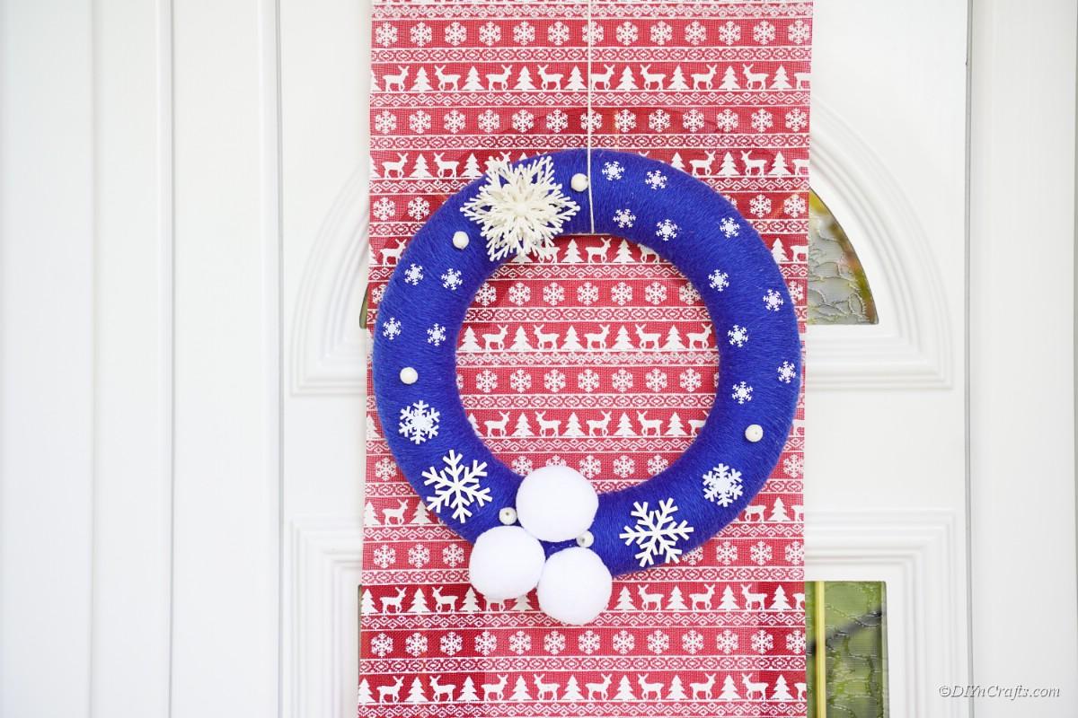 blauer Weihnachtskranz, der über rotem Geschenkpapier hängt