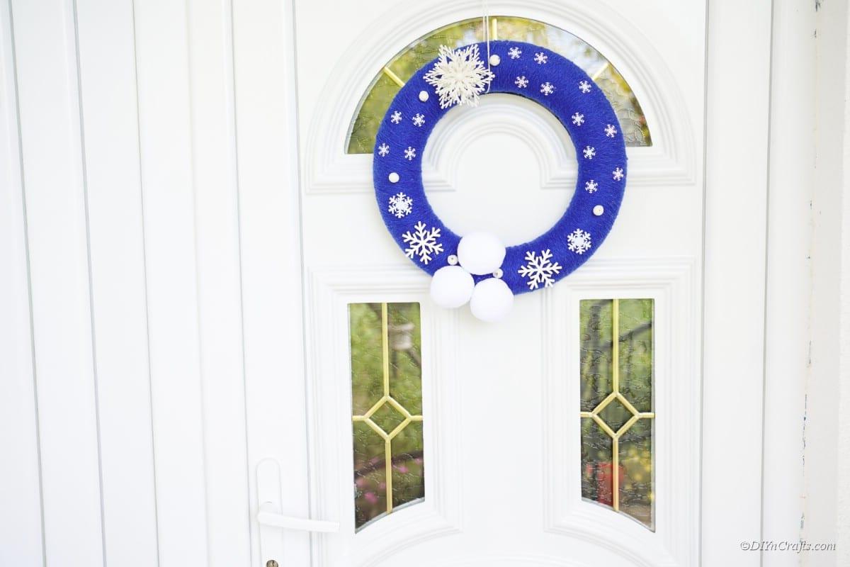 blue snowflake wreath hanging on front door