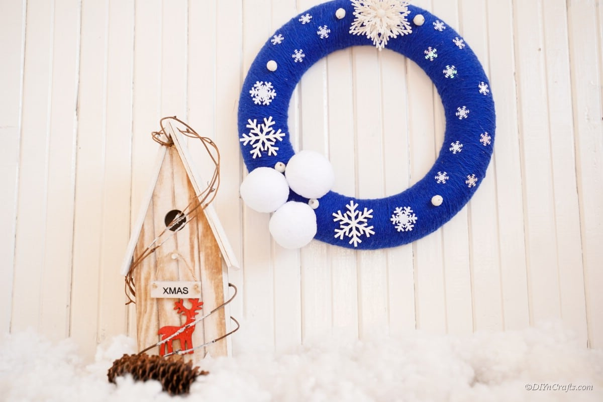 snowflake wreath winter decoration next to a small wooden house