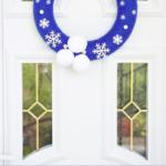 Blauer Schneeflockenkranz, der an einer Tür hängt