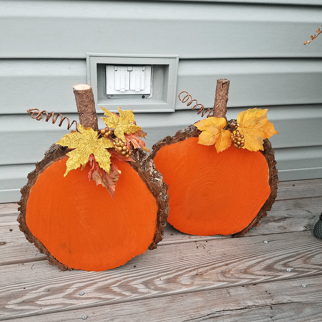 Wood pumpkins by house wall