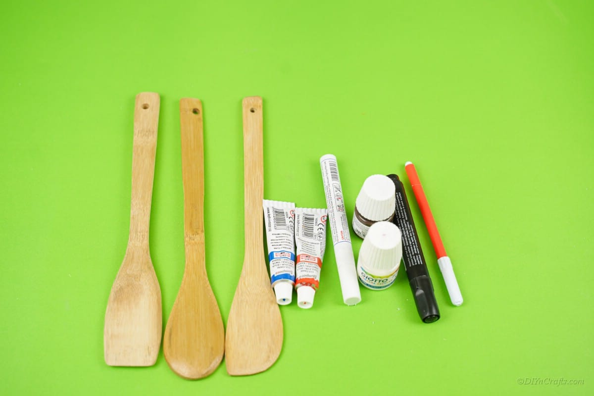 Craft supplies wooden spoons paint markers on table