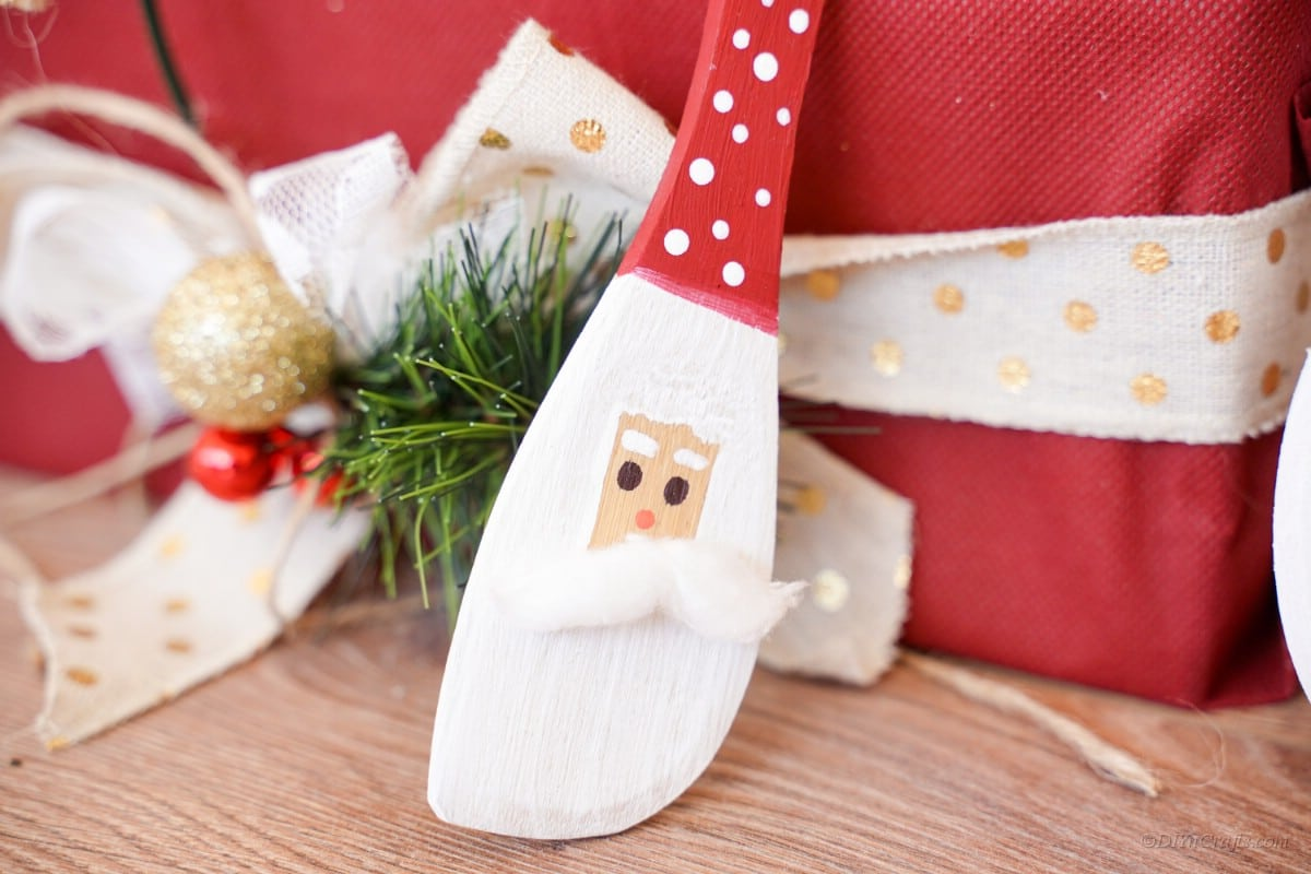 Santa painted character spoon cleaning on present