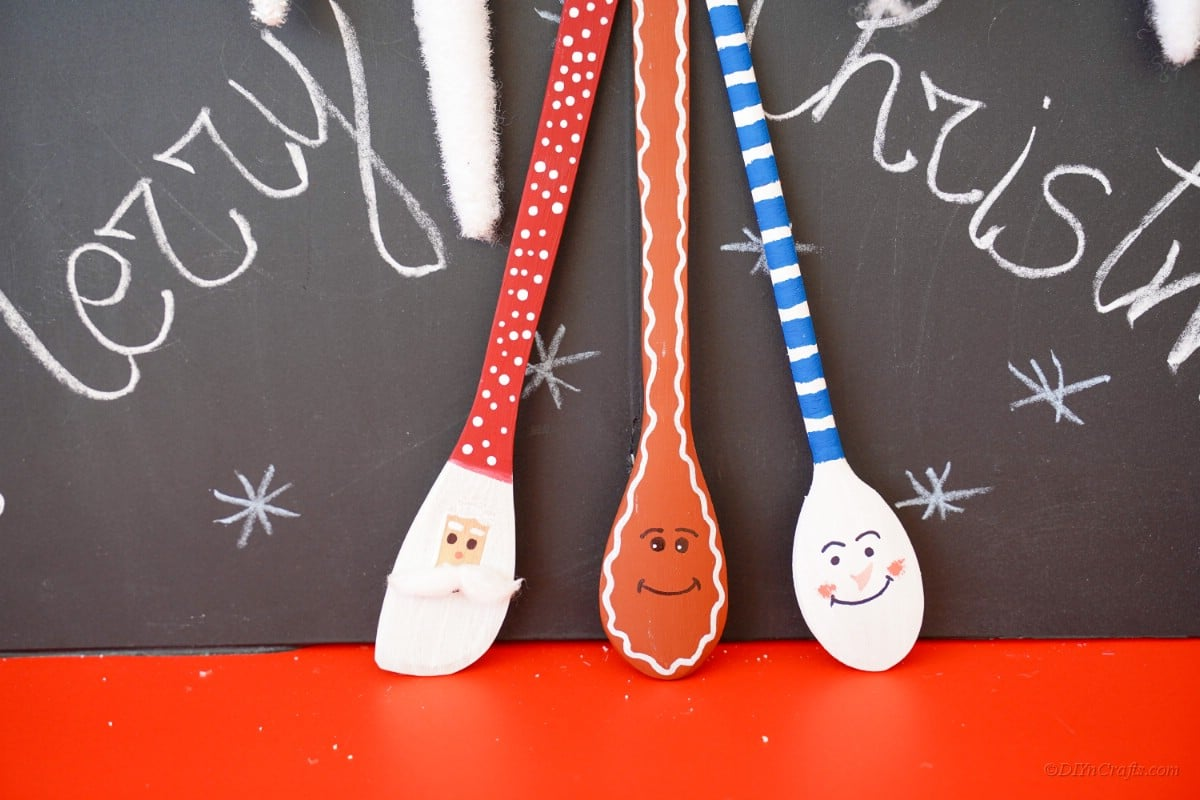 Christmas character wooden spoons in front of chalkboard