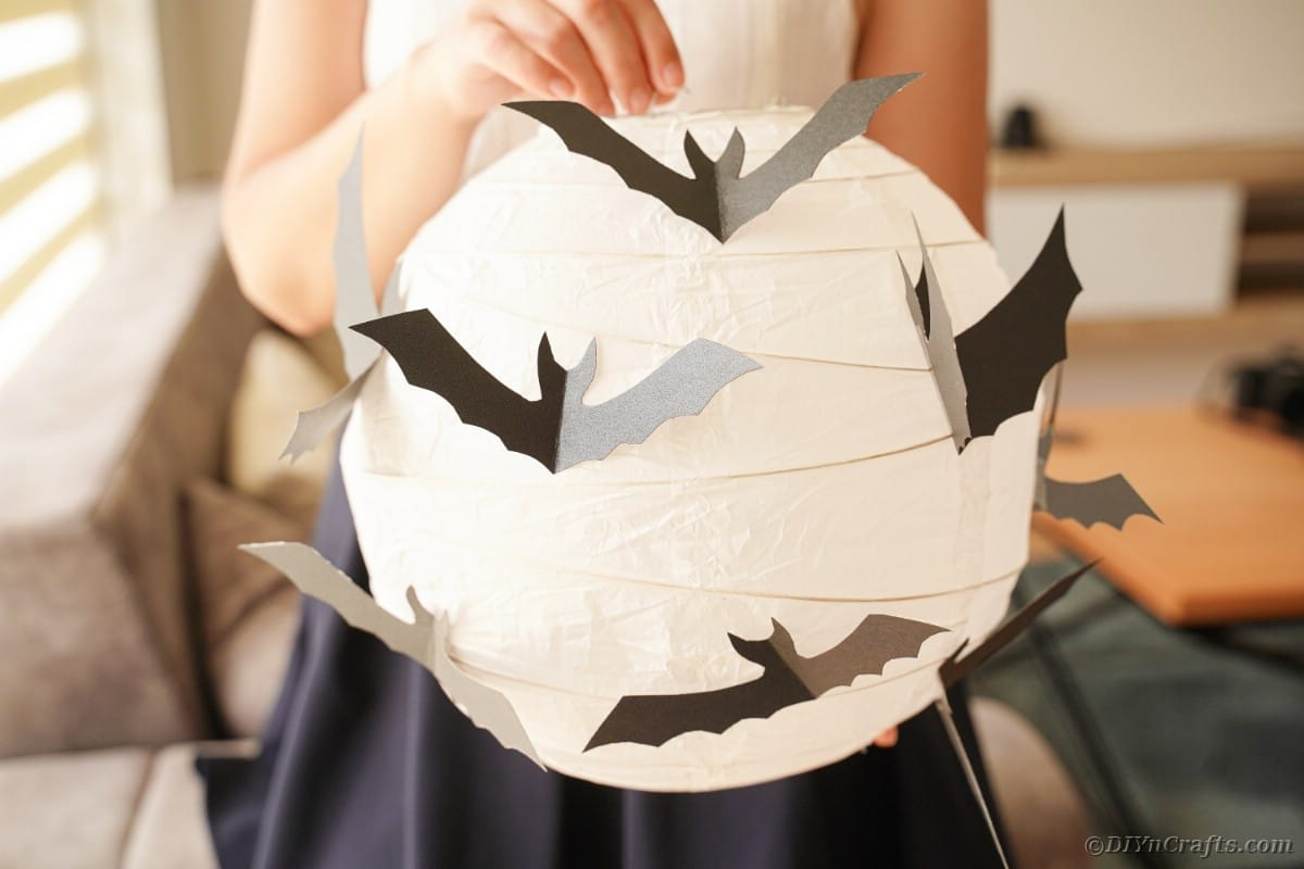 an holding paper bat lantern