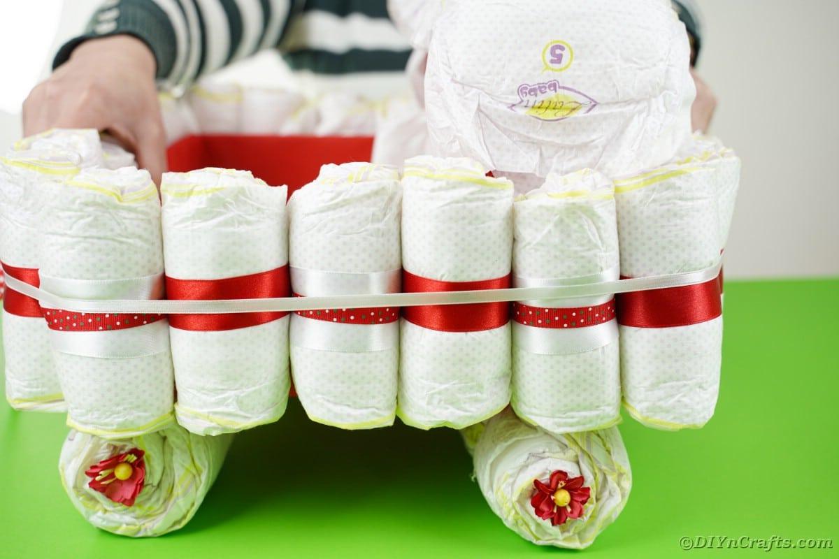 Sitting bassinet onto diaper rolls
