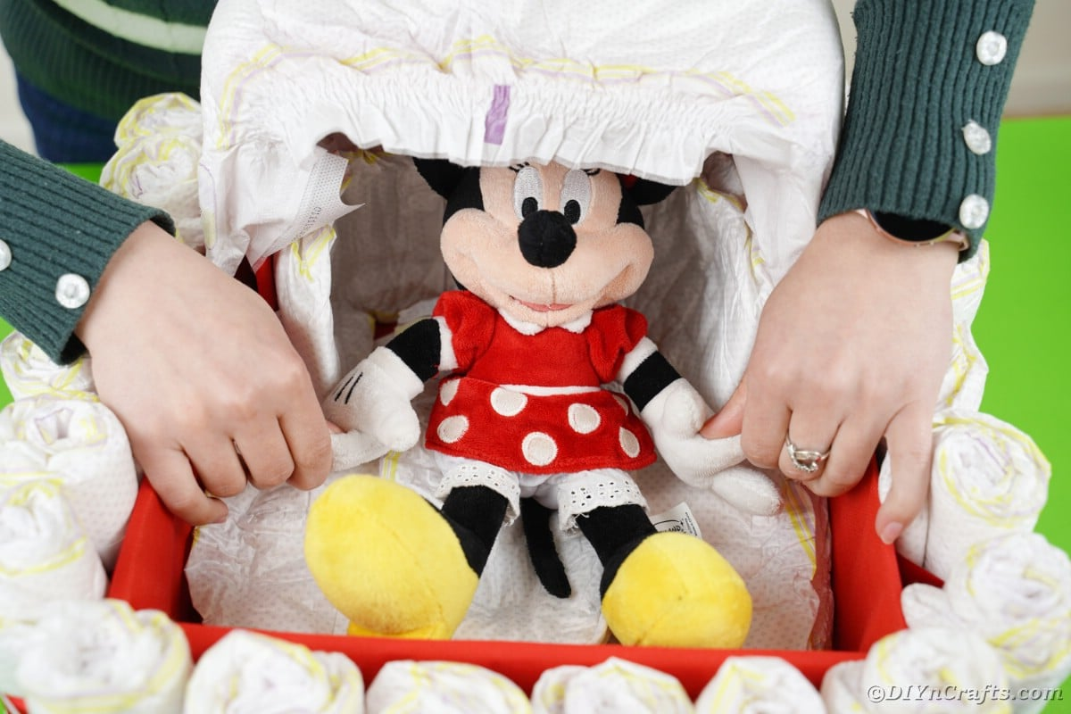 Placing Minnie Mouse in bassinet