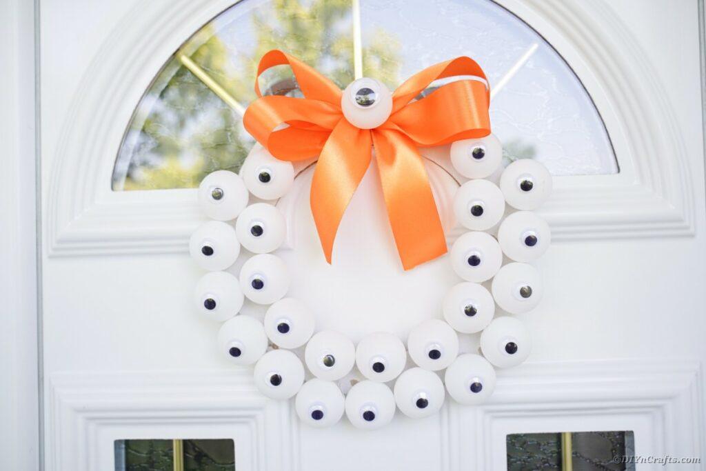 Augapfelkranz, der an weißer Tür hängt