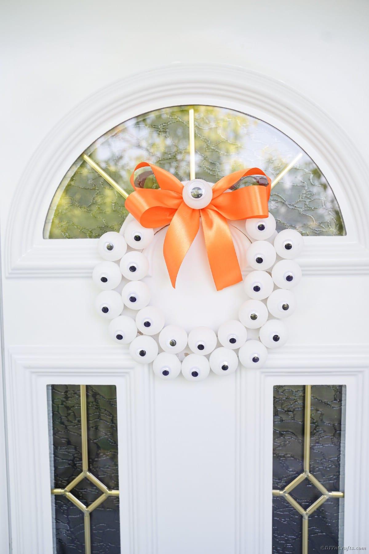 Eyeball wreath hanging on white door