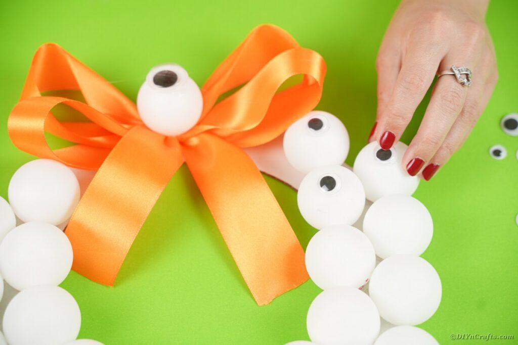 Adding googly eyes to wreath