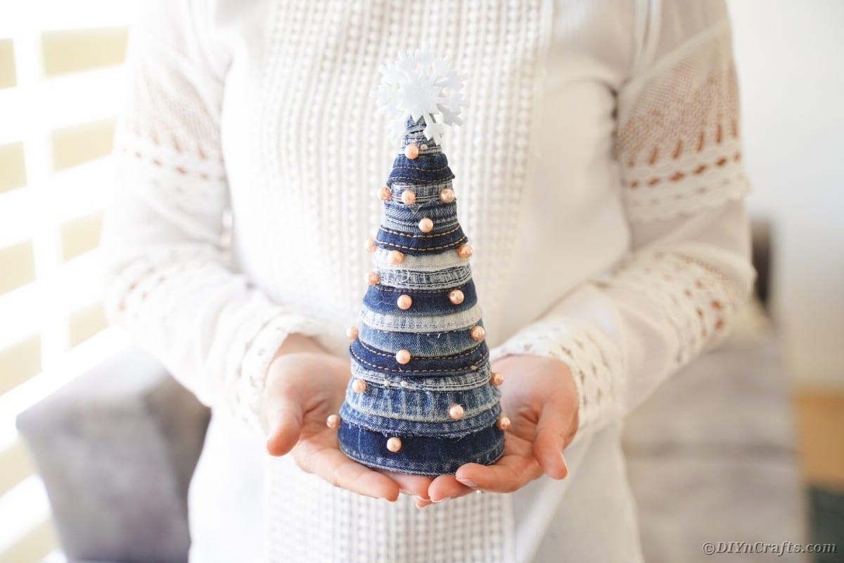 Woman holding mini denim tree