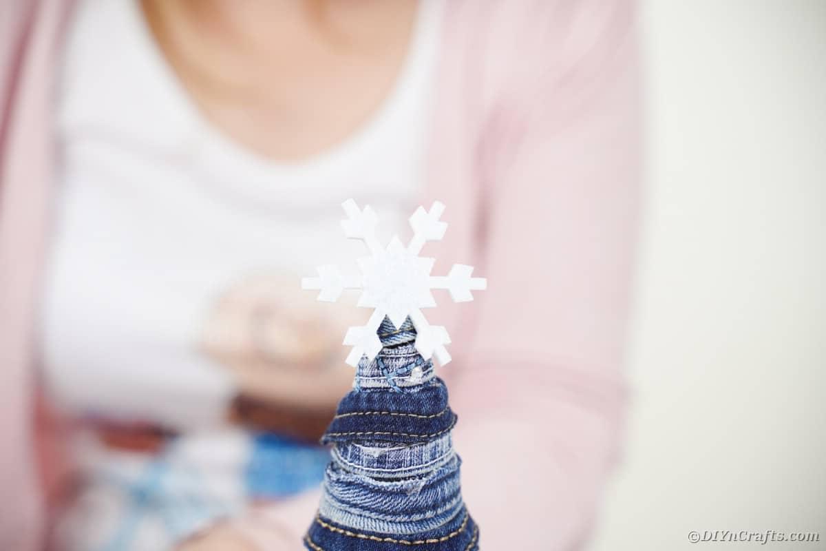 Gluing snowflake on denim tree