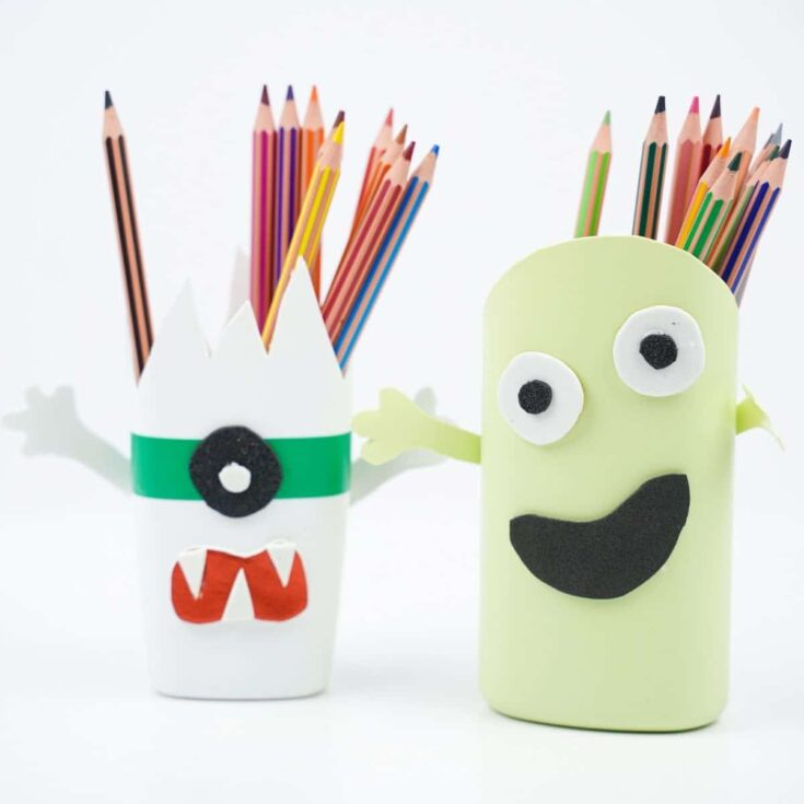 Monster pencil holders on white surface