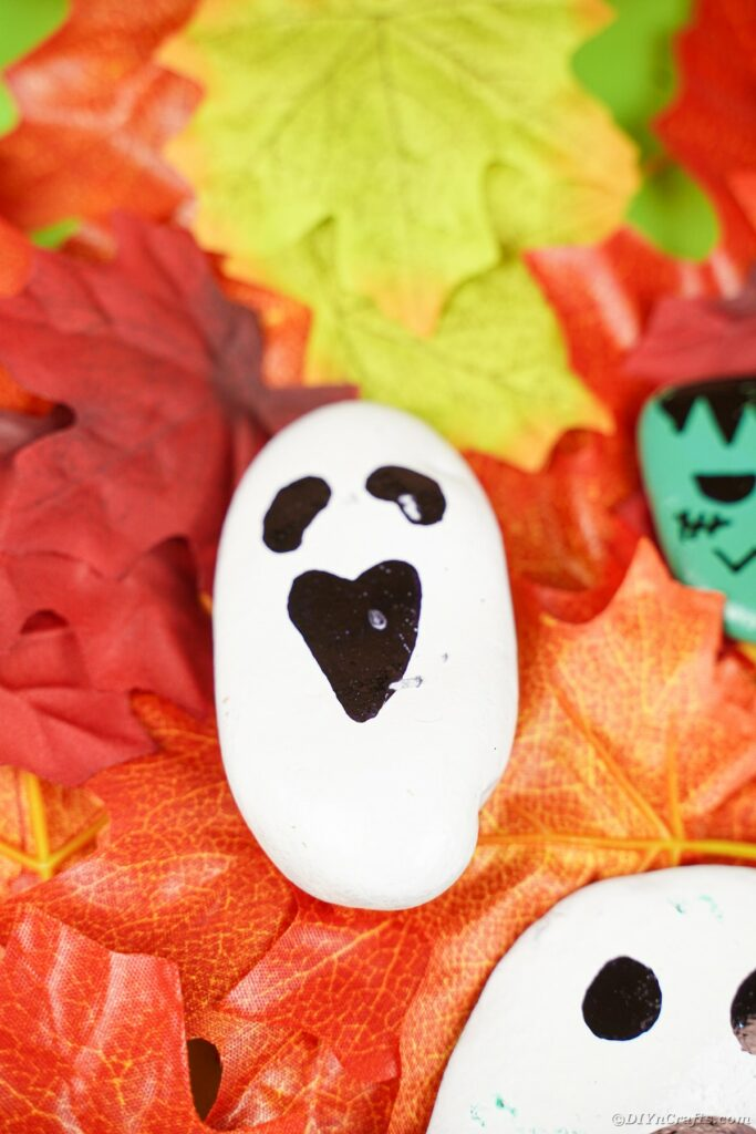 Ghost painted rock on leaves