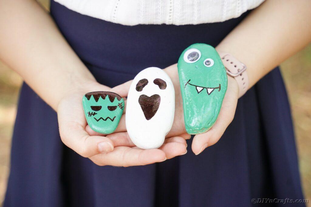Woman holding painted Halloween rocks