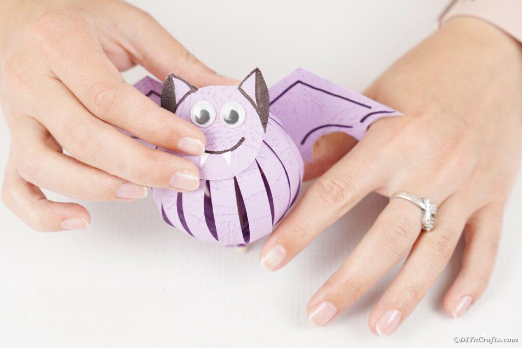 Woman holding purple paper bat