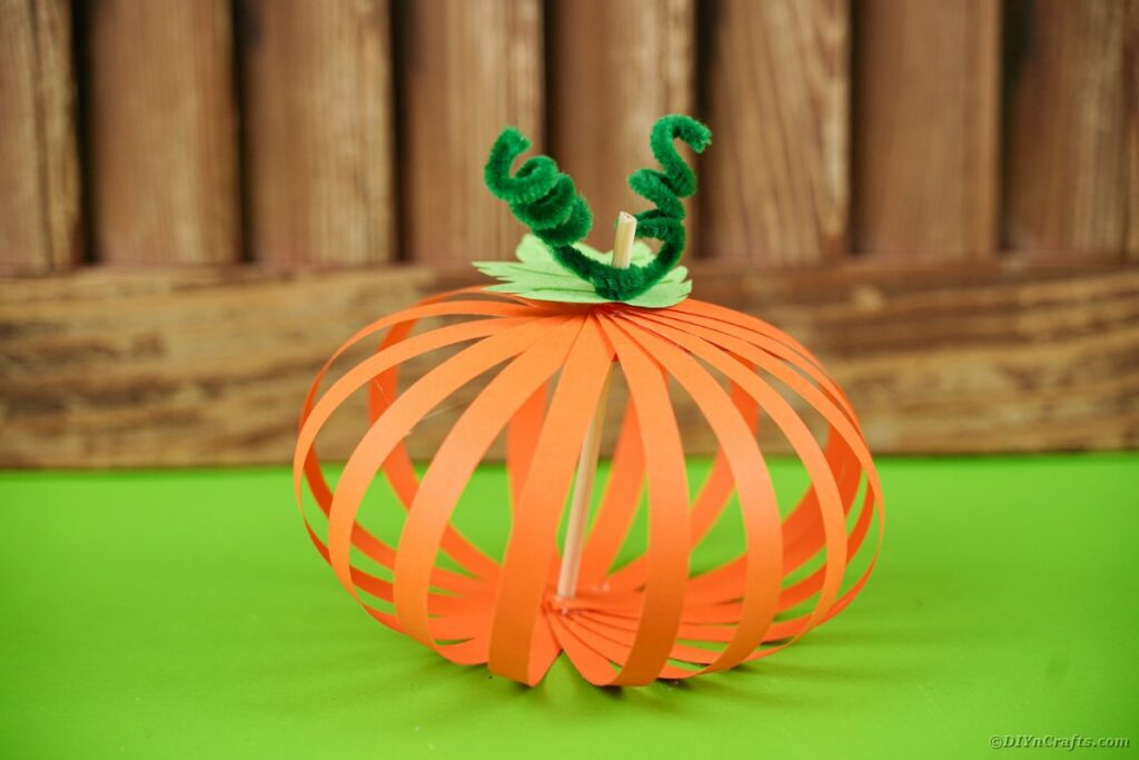 Paper pumpkin on green table