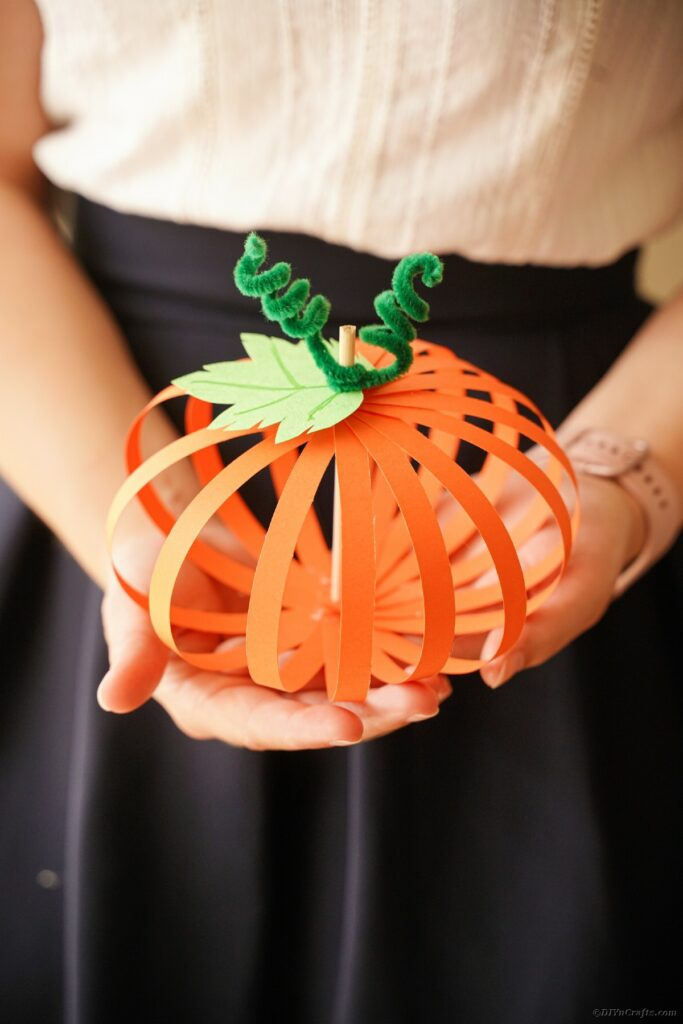 Woman holding paper strip pumpkin