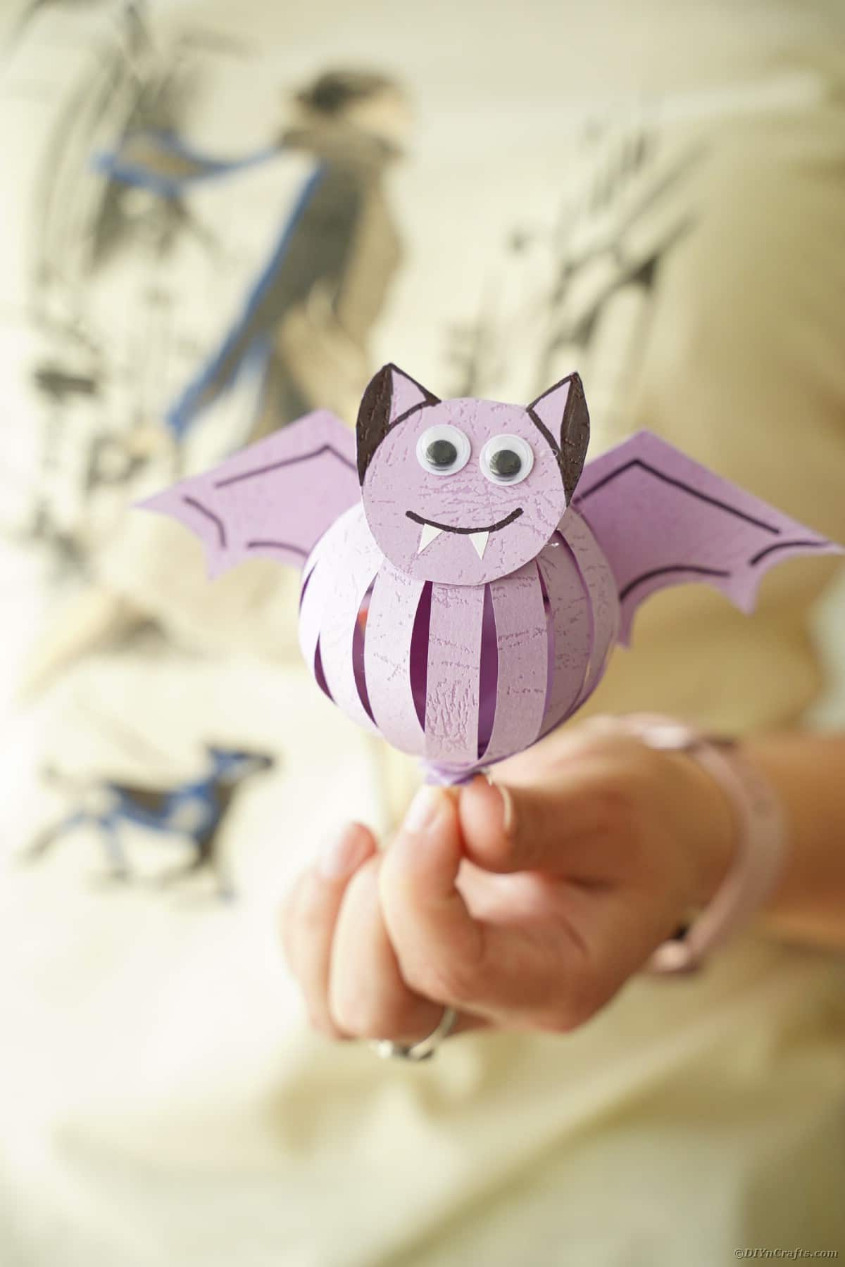 Woman holding purple paper bat