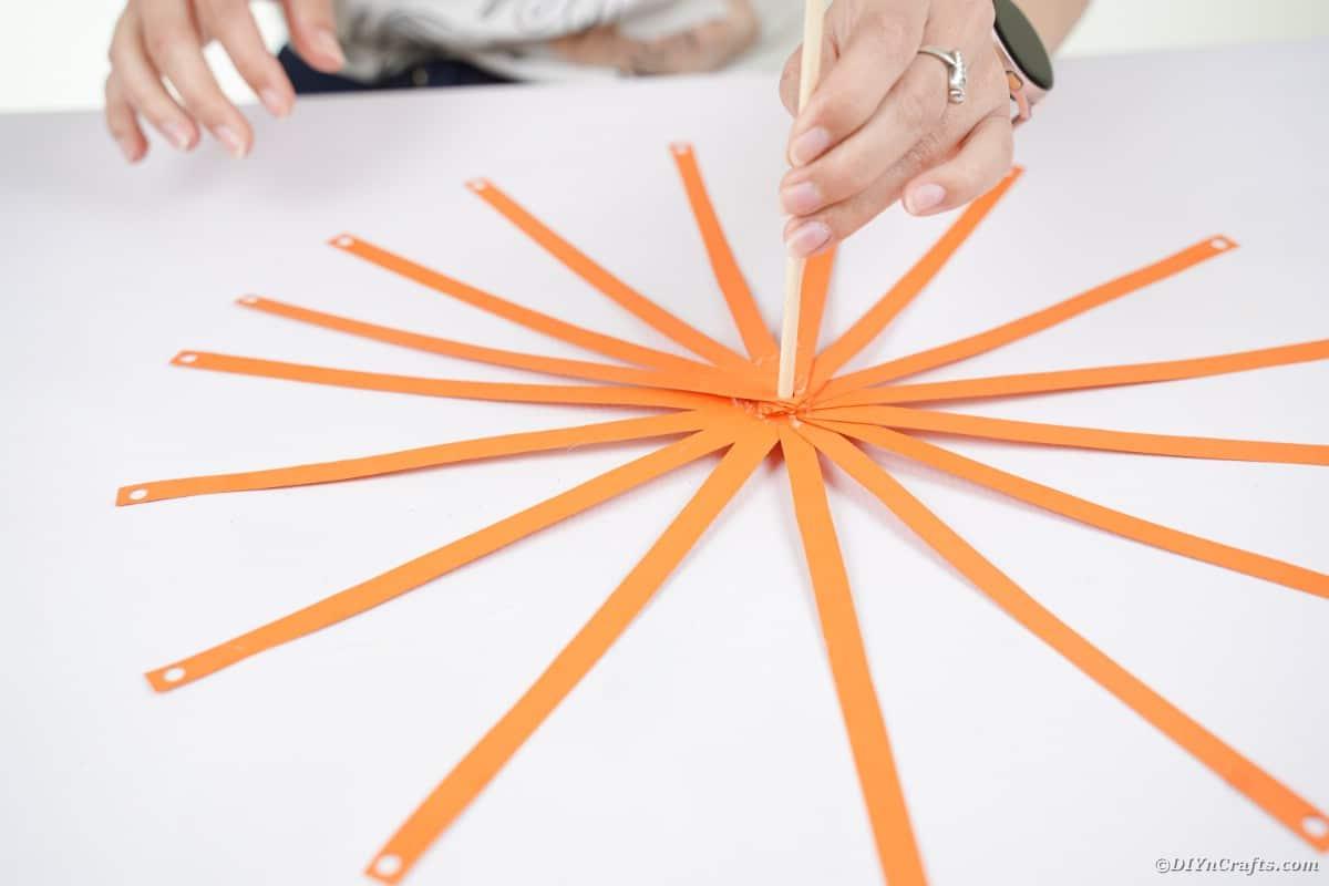 Orange paper strips around dowel