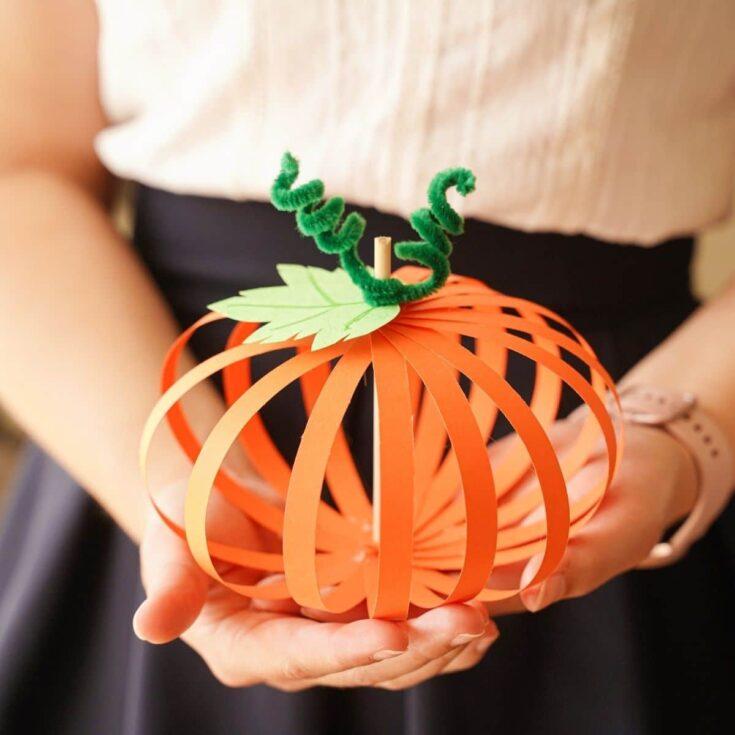 Woman holding paper strip pumpkin