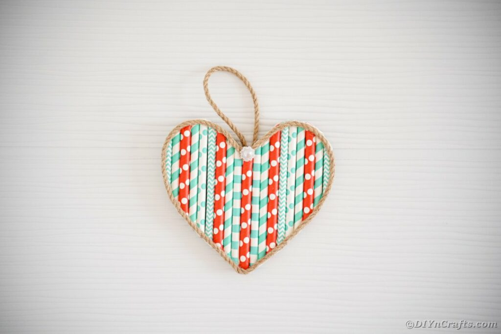 Paper straw heart on white wall