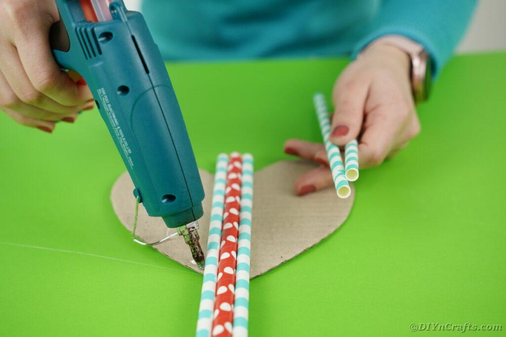 Gluing straws onto cardboard heart