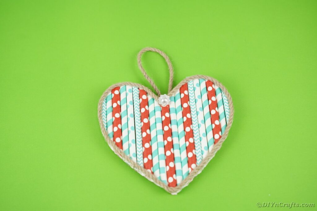 Paper straw heart on green table