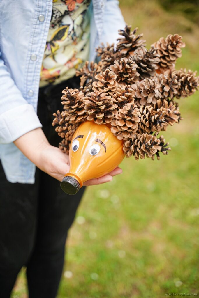 Woman holding a hedgehog made of pinecones