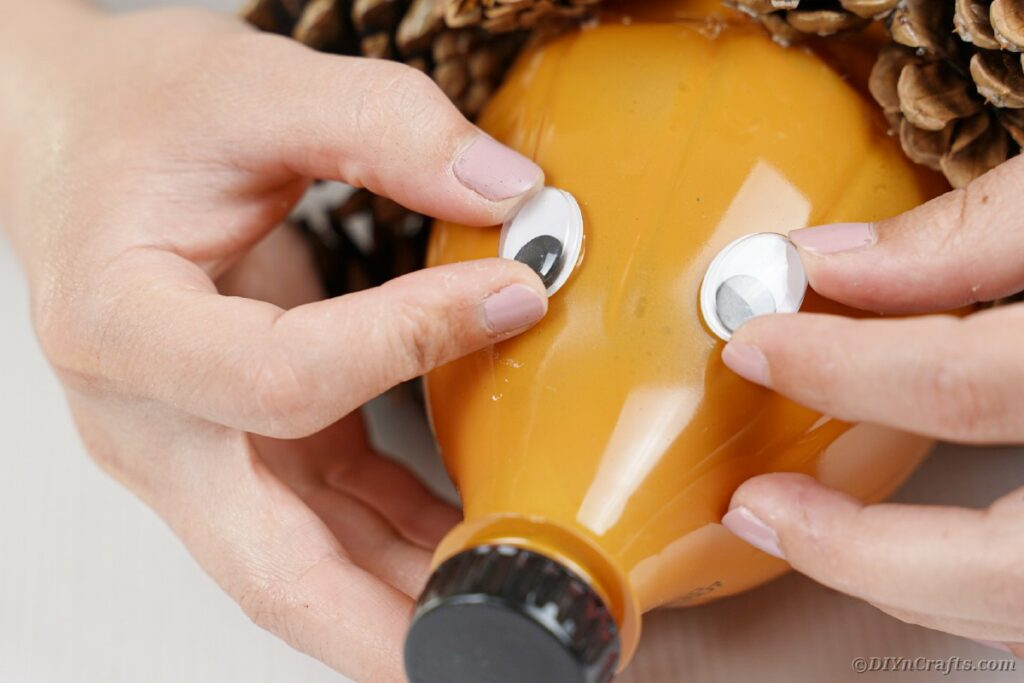Gluing eyes onto orange bottle