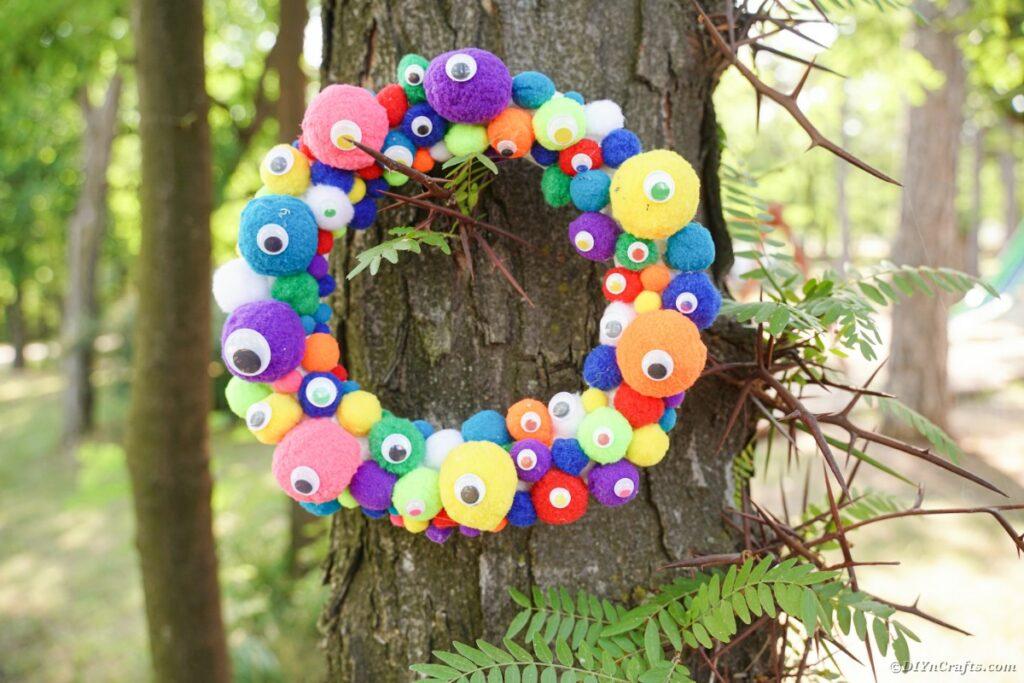 Colorful pom pom wreath on tree
