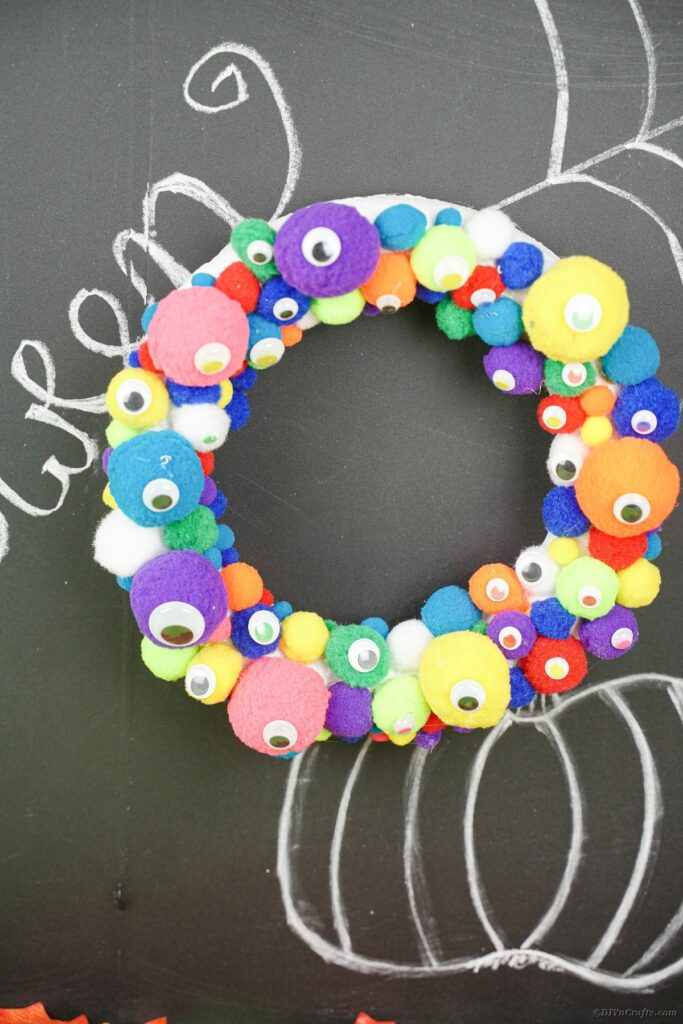 Pom pom wreath on chalkboard