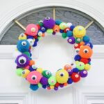 Colorful monster eye wreath on white front door