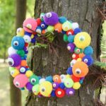 Colorful pom pom wreath on tree