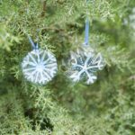 Snowflake ornaments in evergreen tree