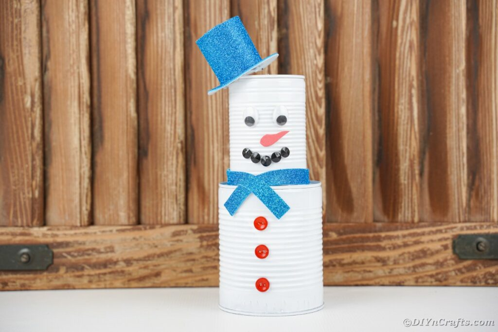 Tin can snowman by wooden wall