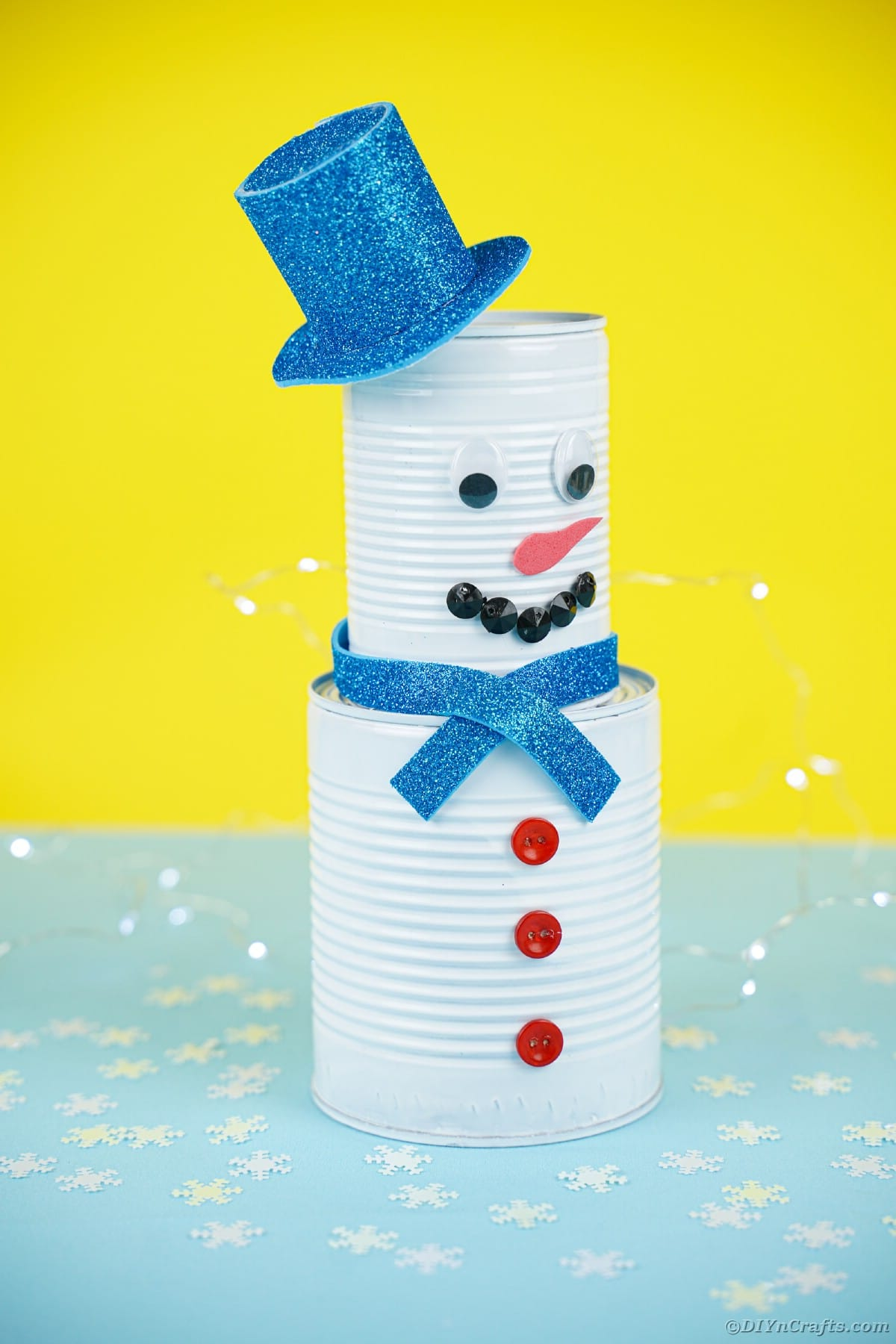 Tin can snowman against yellow background