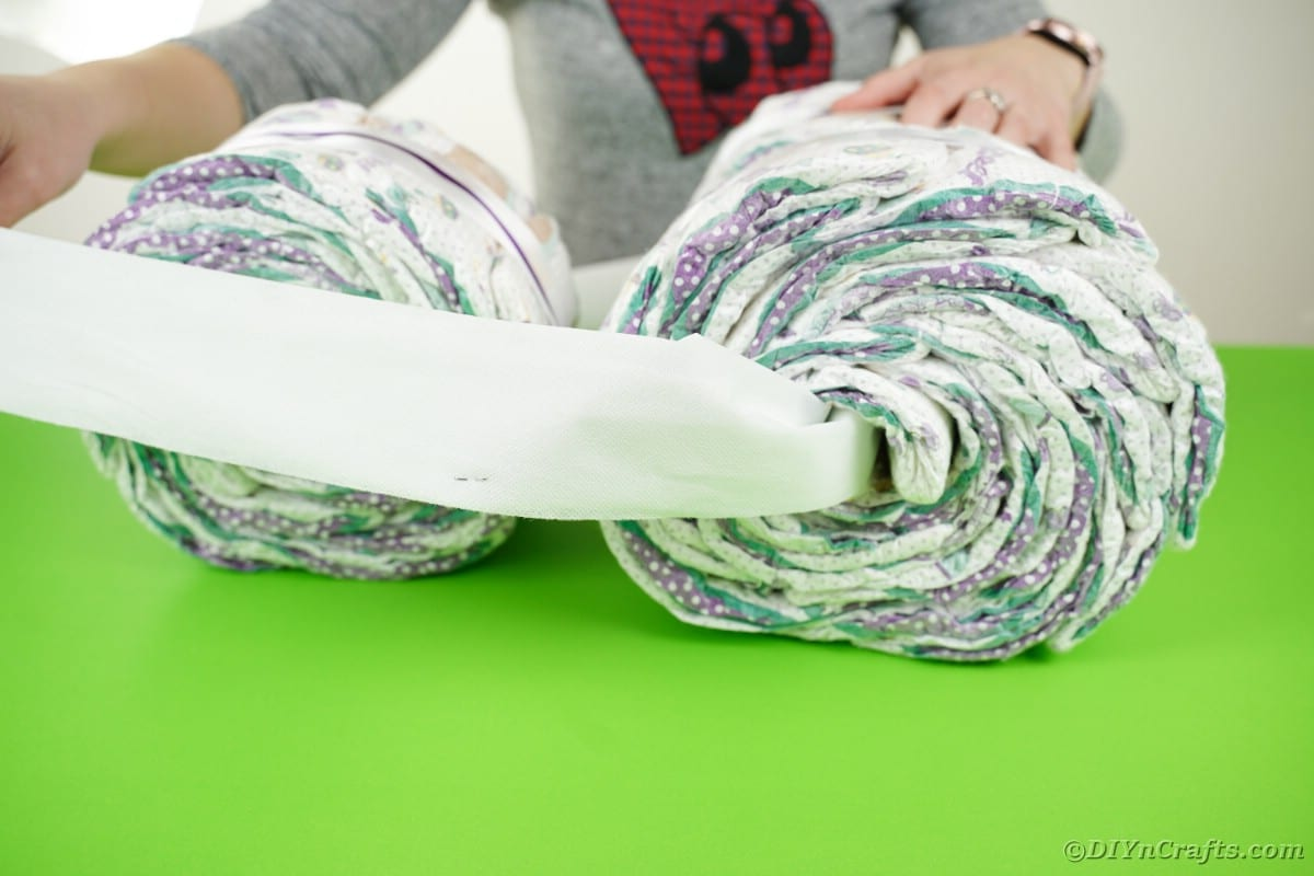 Running tissue paper through diaper rolls