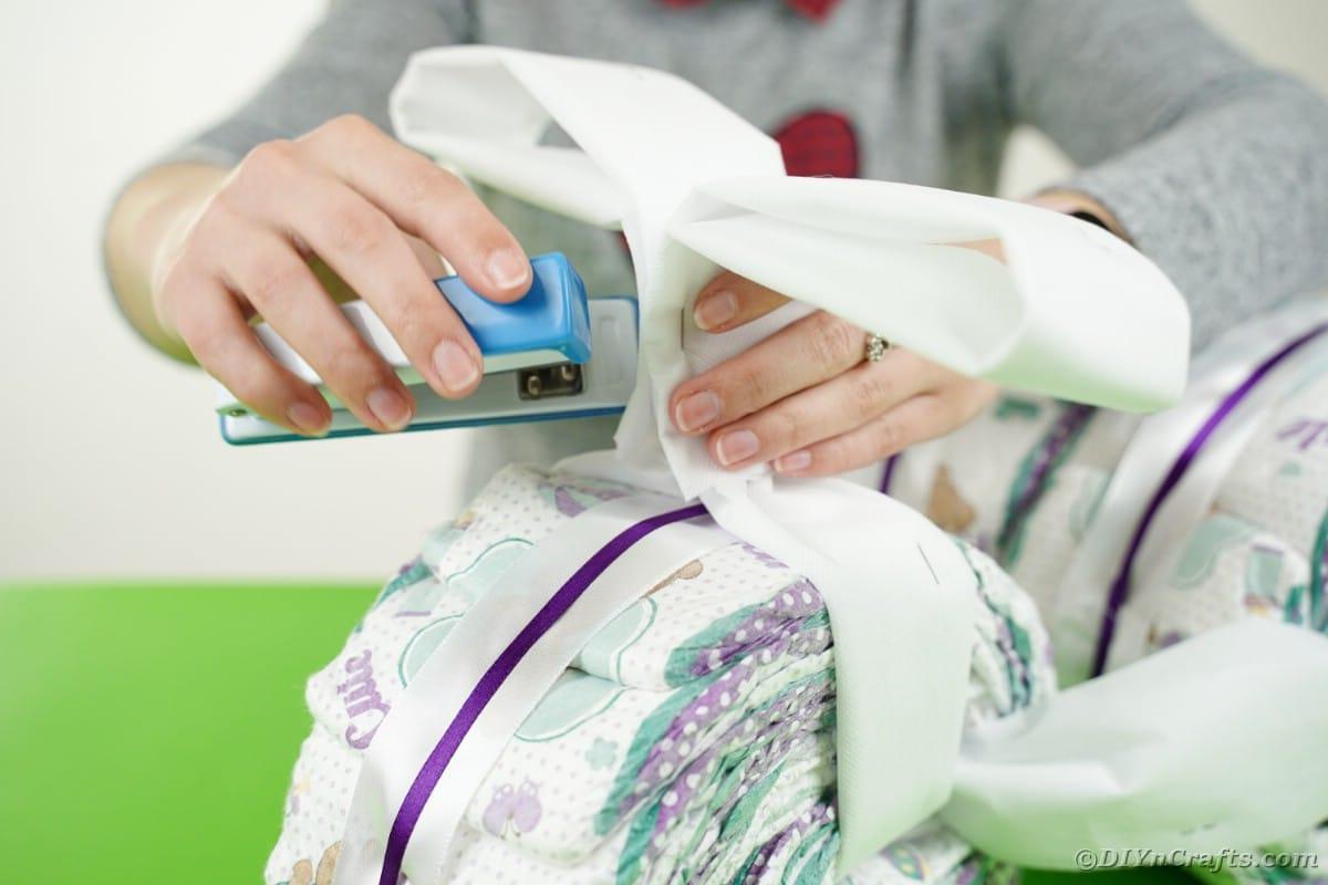 Stapling paper above diaper roll