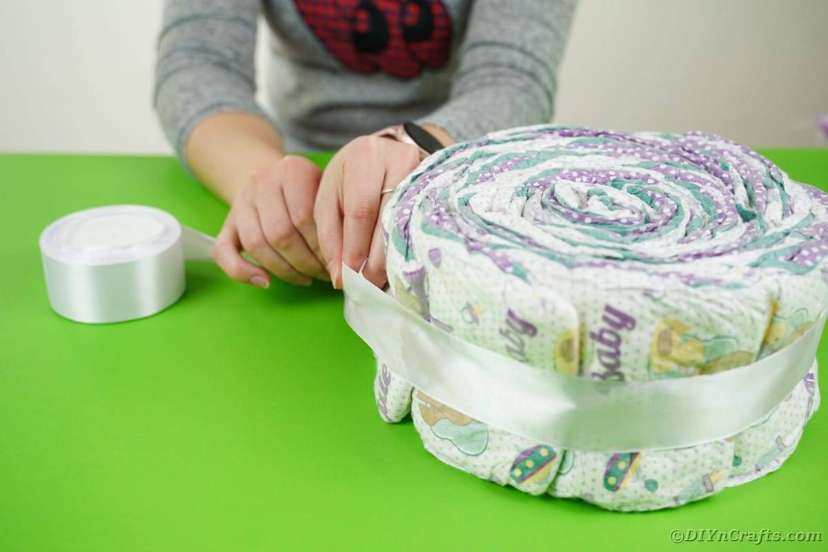 Wrapping roll of diapers with ribbon
