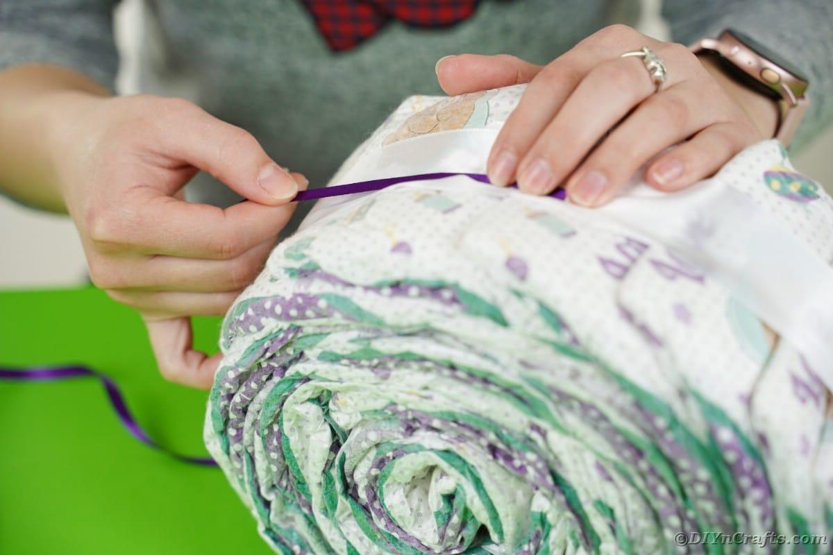Adding purple ribbon to diaper roll