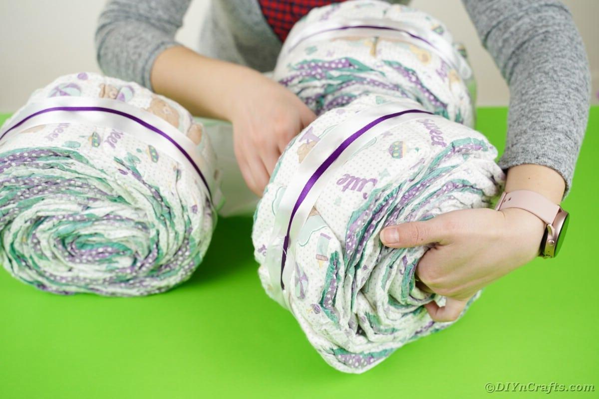 Sliding tissue paper through middle of diaper rolls