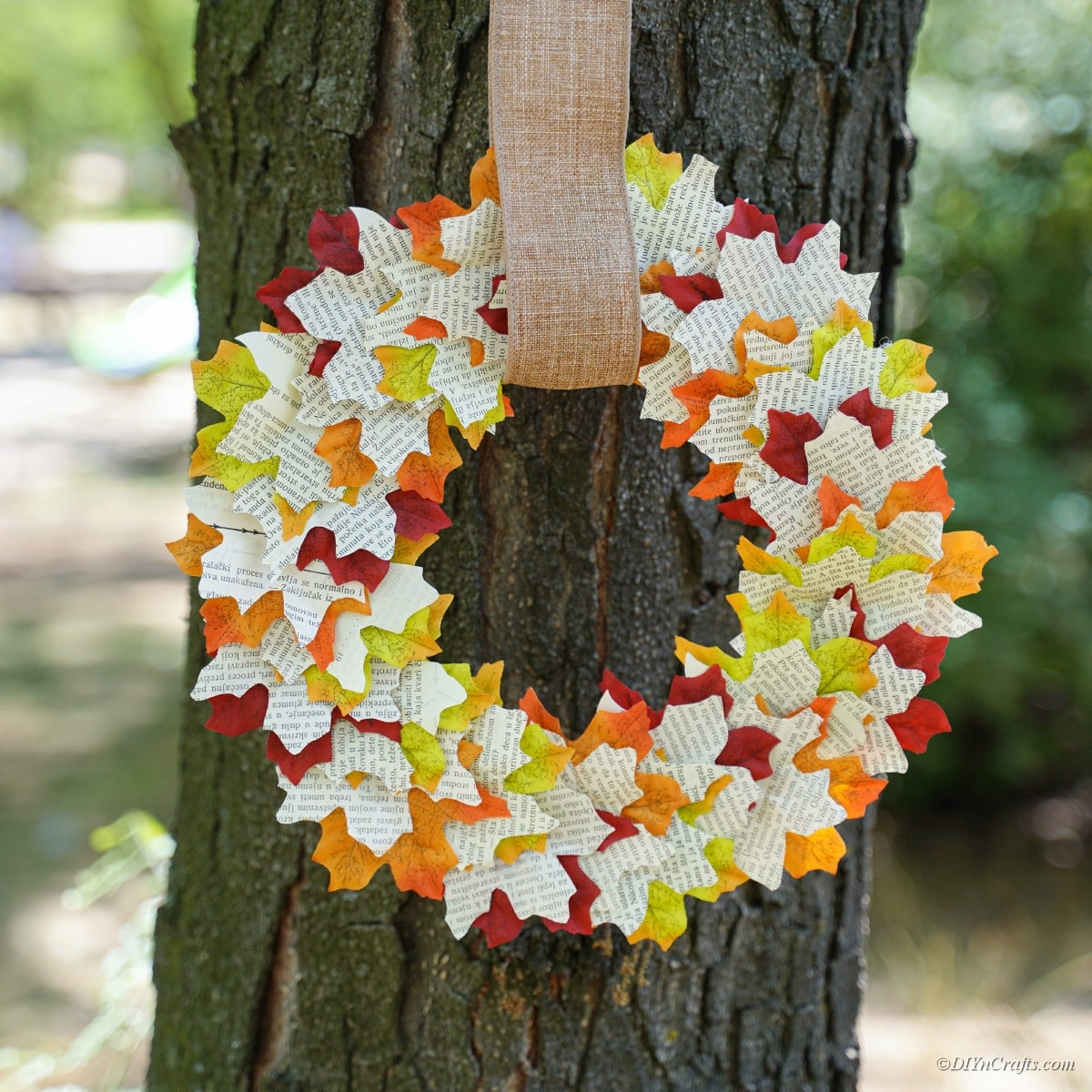 Finished fall leaf wreath hung on a tree outside.
