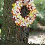 Herbstkranz aus Blättern und recycelten Büchern, die an einem Baum hängen