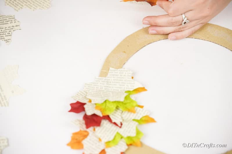 glueing pieces onto cardboard craft on table