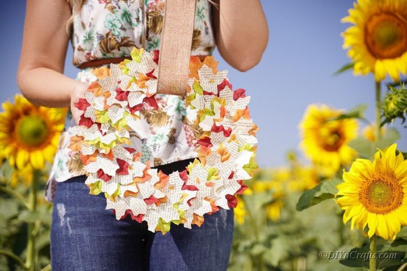 woman holding DIY wreath in sunflower field