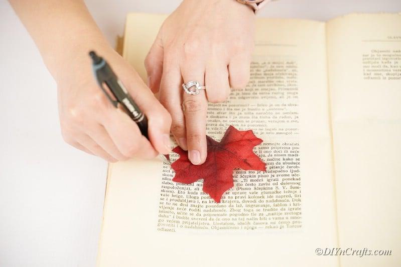 Frau schneidet Blatt auf Buchseite